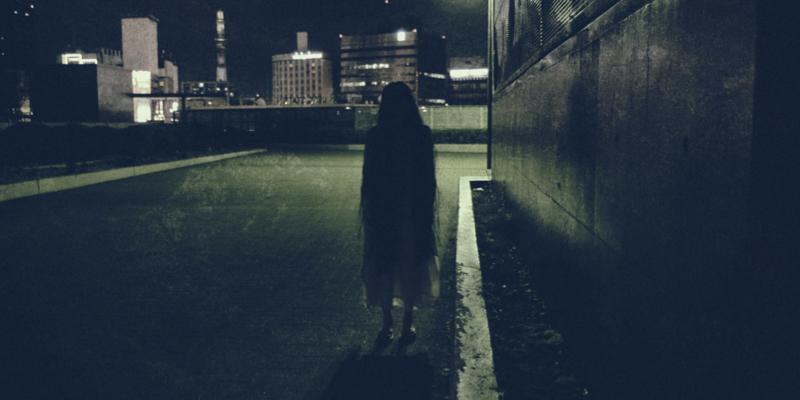 真っ暗な路地に立つ女