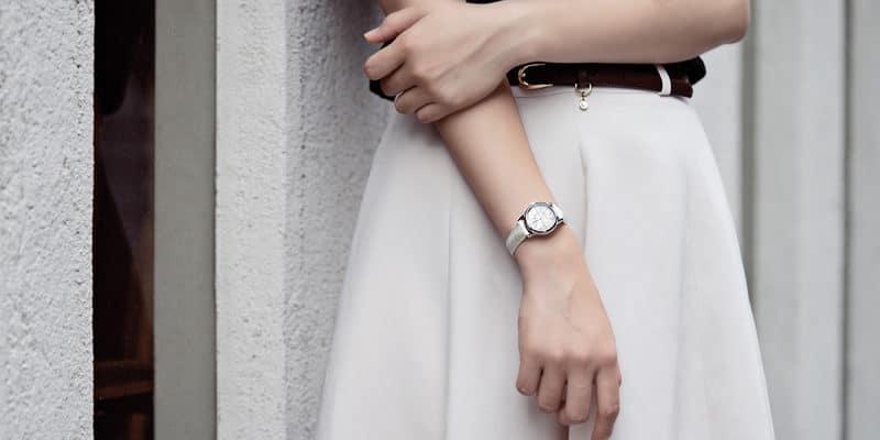女性が腕時計をして立っている姿