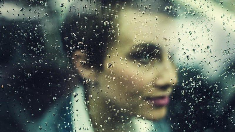 水滴のついた窓と女性