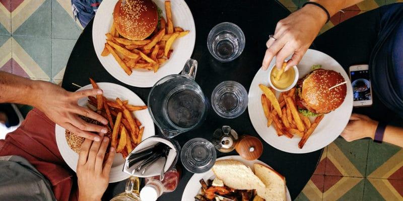 円卓とハンバーガーを食べる人達