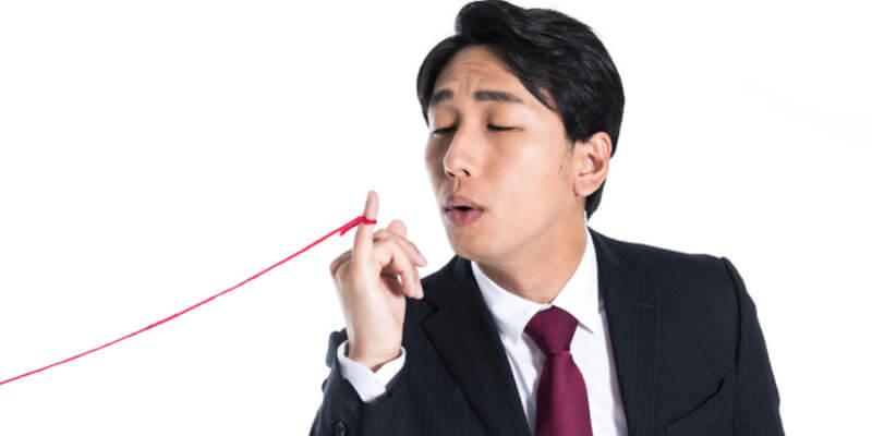 小指に赤い糸を巻いた男性